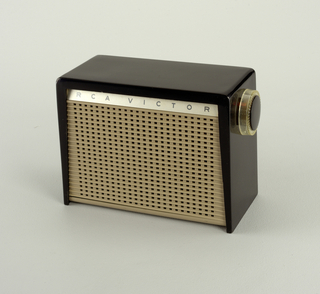 "Rectangular box radio with black cover and tan speaker on face. Above speaker, band with logo: ""RCA VICTOR"". Right side, round dial."