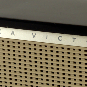 """Rectangular box radio with black cover and tan speaker on face. Above speaker, band with logo: """"RCA VICTOR"""". Right side, round dial."""