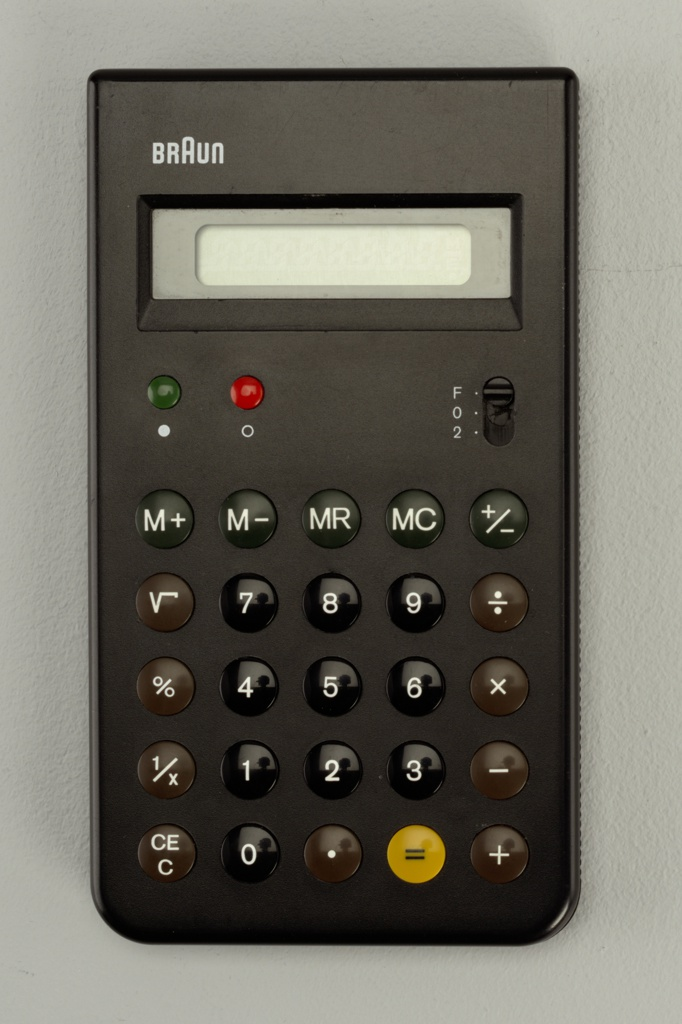 "Flat, black, upright rectangular form, the ""BRAUN"" logo in white letters at top left, above rectangular window for numercial read-out; below window, at left, two small slightly domed buttons: green ""on"" and red ""off,"" with decimal place switch at right, all above five rows of slighly domed black, brown, and yellow function and number keys."