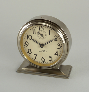 Circular alarm clock with white dial and metal case, curved base, alarm shut-off on top. Beveled edge on surround and base. Contrasting black numbers, hour, minute and second hands.