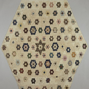 """Six-sided table cover made up of small hexagons in the  """"Garden Path"""" pattern. Beautifully executed with close attention paid to the placement of printed motifs within the cut pieces. Lined with yellow and white seersucker (a later addition). Some paper patterns intact on the inside."""
