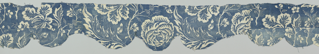Long valance-shaped fragment of coarse cotton. Design is incomplete, but shows a large floral motif and foliage. Background is blue and the design is reserved in white with blue accents and interior lines. Parts of the foliage are outlined in small white dots, and larger leaves contain interior decoration of white dots. The fragment might be the lining of a valance and is pieced with lighter shades of the same design to make a scalloped shape.