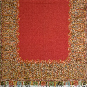 Shawl with a red center and a multicolored cone and lotus border design. Fringed on two ends. Long sides have a narrow green border.