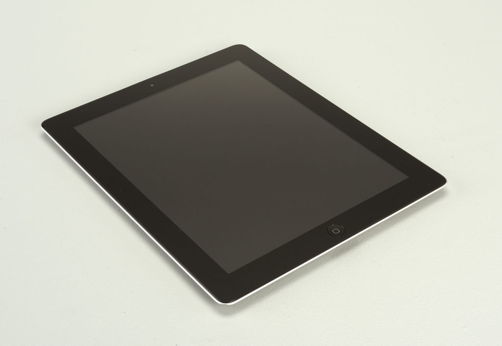 """Rectangular aluminum tablet computer with rounded corners; front composed of flat screen surrounded by black border; """"home"""" button in center front band under screen; camera lense mounted in band above screen. Reverse: Apple logo in black in center of  of housing; small controls near left top; additional camera lense mounted in top left corner of housing."""