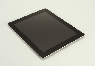 "Rectangular aluminum tablet computer with rounded corners; front composed of flat screen surrounded by black border; ""home"" button in center front band under screen; camera lense mounted in band above screen. Reverse: Apple logo in black in center of  of housing; small controls near left top; additional camera lense mounted in top left corner of housing."