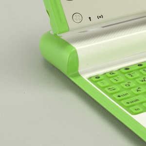 Open: two green panels flip up at front coners to open cover, clam-shell style, revealing LCD screen flanked by two pierced circular speakers and function buttons, surmounting bright green rubber keyboard above white trackpad; USB, headphone, and microphone ports on side of screen. When in the upright position, the green corner panels, reminiscment of animal ears, act as wi-fi antennas. Closed: flat, off-white rectangular form with green edging, wide rectangular slit as carrying handle at one end, flanked by two holes. Light green plastic X and red circle recessed in cover.