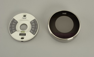Large circular face, black when power is off, surrounded by circular, matte stainless steel housing with control ring around face.