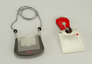 Dark grey body of roughly square form with overlapping translucent screens surmounted by a small circular camera lens in silver colored housing, hinged to allow screen to pivot up.  On reverse, a swiveling pear-shaped red and silver grip containing speaker and earphone.  Two metal rings on upper corners of body for mounting on neck chain.