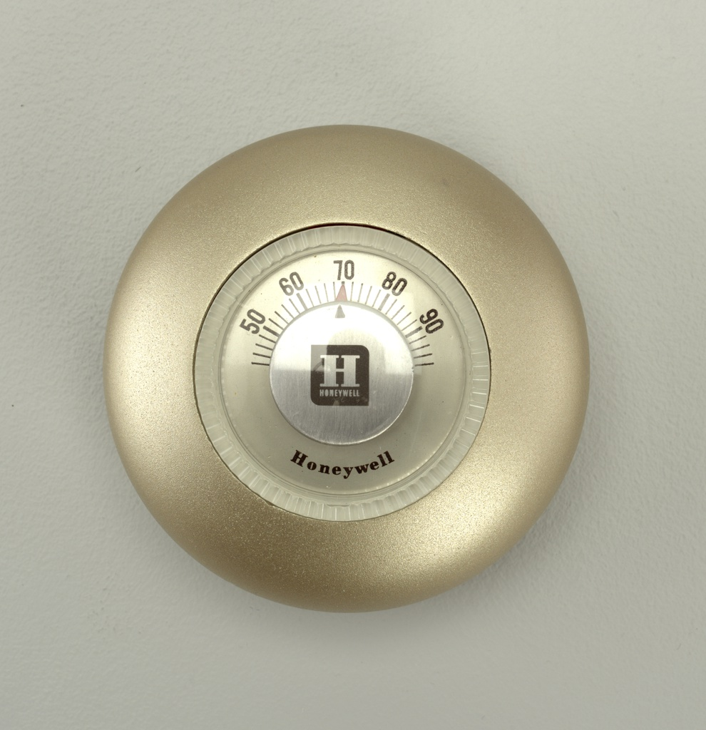 Dome-shaped, matte gold plastic housing surrounding circular thermometer with clear plastic dial.  Dark brown callibration numbers on upper portion of thermometer.