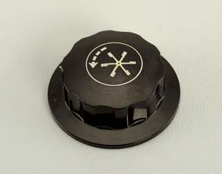 Black knob with white six pointed star and arrow pointing counter-clockwise; related to designs for John Deere