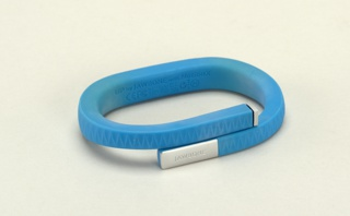 "Slim blue band coiled to fit around the wrist; zig-zag pattern on surface, thin metal cap at one end, metal strip with the word ""JAWBONE"" at the other."