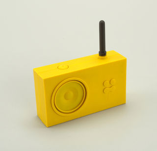 Block-like, rectangular yellow silicone rubber-covered body with short cylindrical dark gray antenna top right; face with circular speaker on left; volume and AM/FM buttons on right. Antenna rotates to act as tuner.