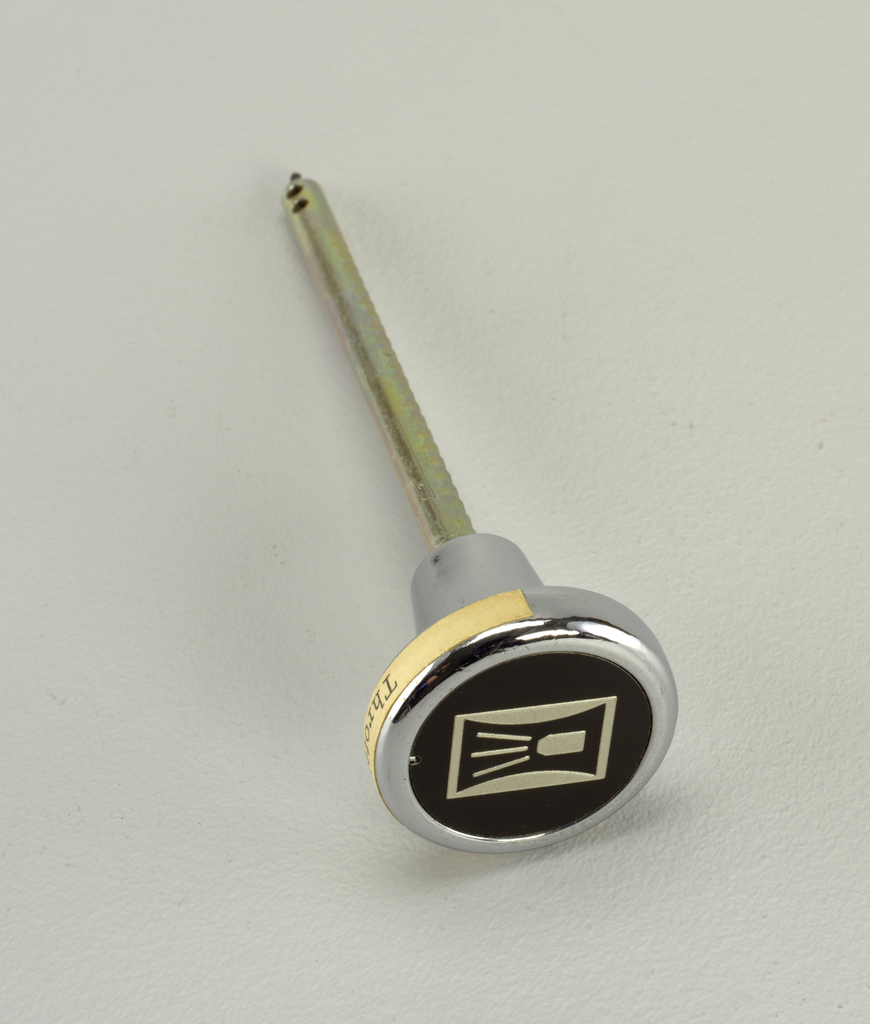 knob of chrome-plated metal with symbol in silver-grey on black background; throttle