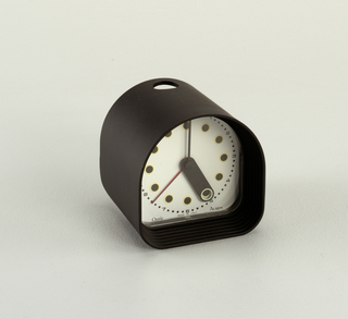 """Black, arched case; white face with ring of 12 yellow-encircled black """"hour"""" dots surrounded by a ring of corresponding numerals interspersed with small black """"minute"""" dots;  black, lozenge-shaped hour hand with hole at end to reveal """"hour"""" dots, thin black minute hand, thin red second hand.  In small print on bottom of face: """"Optic / MADE IN ITALY / Alarm."""""""