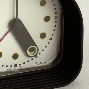 "Black, arched case; white face with ring of 12 yellow-encircled black ""hour"" dots surrounded by a ring of corresponding numerals interspersed with small black ""minute"" dots;  black, lozenge-shaped hour hand with hole at end to reveal ""hour"" dots, thin black minute hand, thin red second hand.  In small print on bottom of face: ""Optic / MADE IN ITALY / Alarm."""