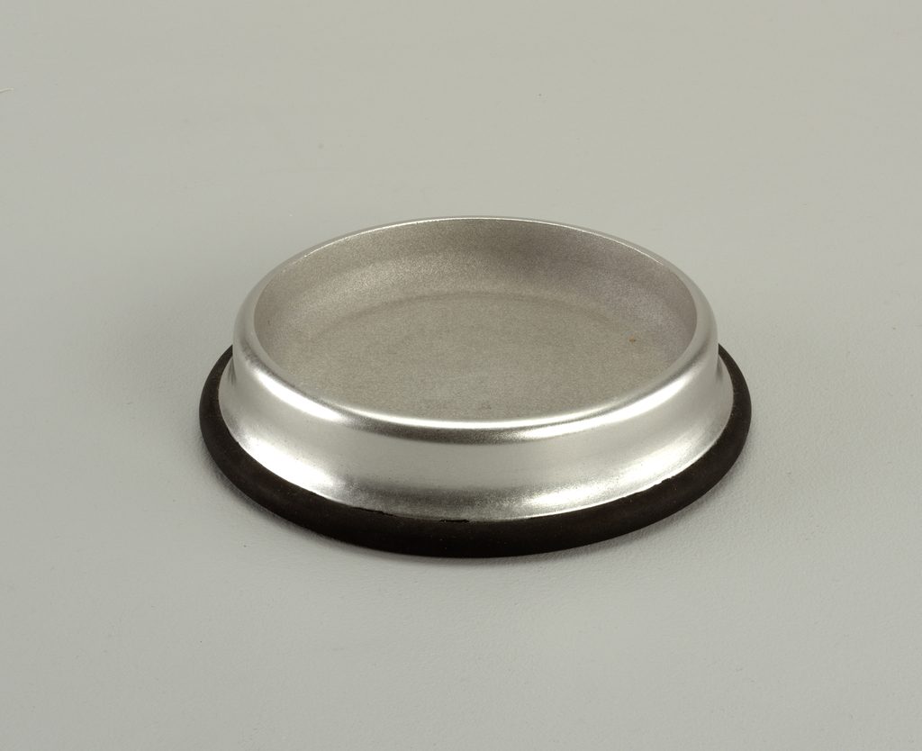 Circular, rimmed aluminum body on black rubber base.
