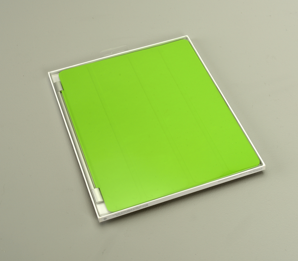 Bright green rectangle with magnetic strip at top to attach to iPad 2 tablet computer; horizontal joints allow cover to fold and form stand for computer when in use.