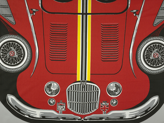 "Bedspread in red, grey, black and yellow of a Spitfire car which covers the entire surface of the bedspread on a black ground. Car conforms to the shape of the bed with an aerial view showing seats, steering wheel, etc. Two corners are curved. On license plate: ""Spitfire, Spreadmobile, Designed by Mr. Sid™, Protected by U.S. & Foreign Patents. U.S. Pat. 3266063."""