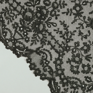 Black triangular shaped shawl with a design of flower sprays, curving motifs and a scalloped border.