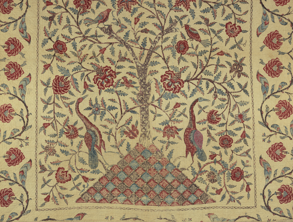 Bedcover showing a central field with trees and a wide border with flowering vine. A tree with exposed roots rises from the point of a triangular mound, and branches about half way up appeared to be sawed off. A vine rises from the mound, crossing and recrossing the tree and bearing large flowers in shades of red and foliage in blue. The flowers exhibit much interior decoration in reserved patterns. Babbler birds are perched amid branches and two long-necked cranes are on the mound on either side of the tree. The mound is made of a series of diamond shapes with a row of red diamonds alternating with a row of blue diamonds. They bear fine inner decoration of fine sprays of flowers reserved in white. The crane at the right of the tree has a back wing which is an applied patch painted in a pattern similar but not the same as that of his companion. A wide border is between two very narrow guard borders decorated with a vine in brown bearing large heavy flowers in red, possibly lotus flowers. Pointed leaves in a chevron of red and blue with outlines of dark brown. Yellow has faded to the extent that the foliage is now blue.
