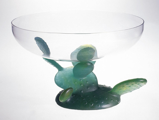A shallow circular clear glass bowl on a green glass base resembling a cactus.