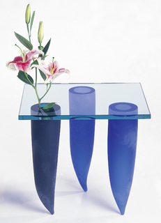 A glass table with three blue legs in the form of cones. The pointed sides are the feet while the wide base hold up the clear square glass table top.