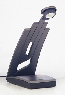 A dark colored lamp with a rectangle base. The top of the lamp composed of multiple rectangle in a vertical arrangement, with the light located on the highest center point with a forward lean.