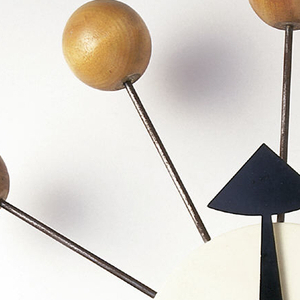 White-painted, circular wooden body; 12 steel spokes radiate around perimeter, end of each spoke punctuated by a wooden ball; sheet metal hands mounted in center of body; triangular form at end of black hour hand, oval form near end of black minute hand, teardrop form at end of slender, red, second hand.