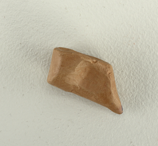 Model for pen grip; brown contoured rectangular form, drawn to a curved point at one corner.