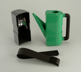 A green plastic watering can in a rectangle shape with rounded corners on half the object. The watering can has a long triangular spout and a large, black, rectangle handle. There is a small circle opening on the top. This watering can fits into another piece as a set.