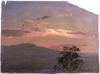 Horizontal view of a mountain range across a valley.  THe top of a tree is shown in the right foreground.  Reddened sky with some clouds.