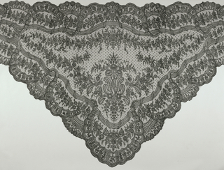 Triangular black silk lace shawl with scalloped edge with design of broad ribbon crossed at regular intervals by narrow leaf. Central floral motif.