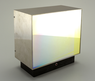 Stainless steel box with mirrored glass face on short blackened metal base. Through the one-way morrored glass are seen five small colored blinking lights and their multiple mirrored images as they rotate around.