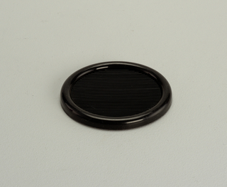 Opaque, black, semi-rigid coaster with 3-inch diameter well
