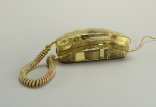 Arched rectangular body, dial handset, and coiled cord made of transparent plastic with electronic components visible.