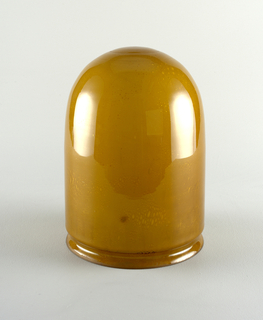 a) Elongated bowl with rounded bottom made of amber glass with bbubbles, opening of bowl fits onto  round brass plate with light bulb holder, when it is held by four screws. b) The plate is suspended by articulated metal sheathing which covers wiring, from c) a smaller circular brass plate which fits against ceiling.