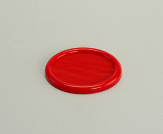 Opaque, red, semi-rigid coaster with 3-inch diameter well