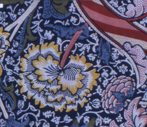 Large-scale design of massive flower heads, curving leaves and stems, broad striped serpentine bands in white, yellow, red, pink, green and blue on a dark blue ground with all-over floral resist pattern. Dotted detail. Plain wide dark blue selvedges.