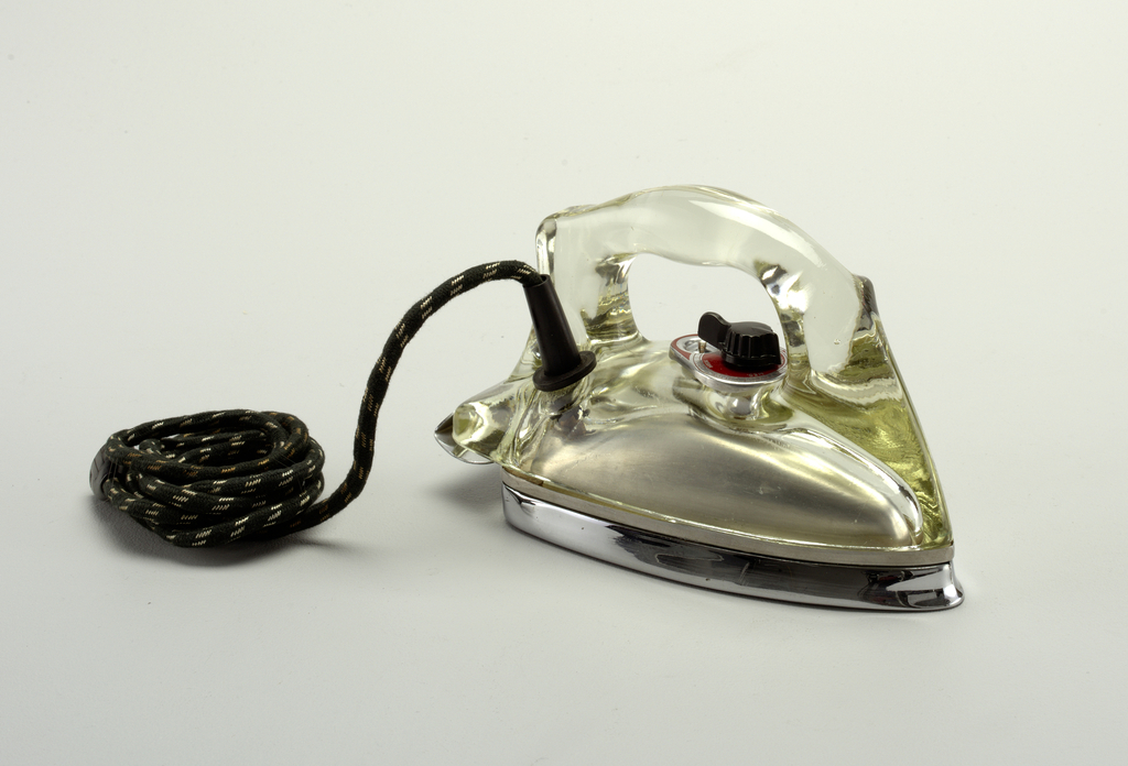 "Broad, oblong wedge-shaped profile comprising one-piece molded transparent glass shroud and handle affixed to white metal soleplate and heel rest. Fabric-covered power cord emerges from tubular rubber flange at top right side. Black plastic dial on red face-plate inscribed:  ""Off, On, Rayon, Silk, Wool, Cotton, Linen,"" and ""Low, Med, High."""