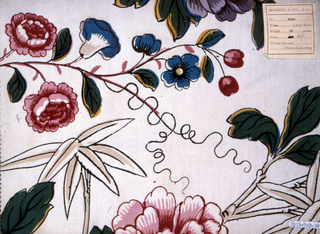 Large scale brightly colored design of flowering branches in Chinoiserie style, including bamboo and tree peony, on white ground.
