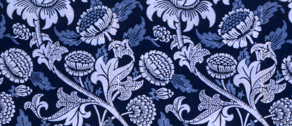 Medium scale design of large flowers on curving stems with small composite flowers scattered between. Some dotted detail. In two shades of pale blue on deep indigo blue ground. Wide plain deep blue selvedges.