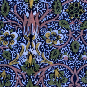 Symmetrical small-scale design of arabesques and ogees formed by twining plant stems, flowers and leaves, in pink, yellow, and green on a dark blue ground with a tiny all-over floral resist pattern.