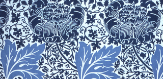 Large flower heads leaning left, and large leaves, on a ground of small-scale, all-over design of flowering vines. In two shades of blue on a white ground.
