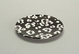 A white abstract design on black plastic circular plate.
