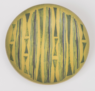 Shallow bowl of reddish clay with some grog added.  Outside glazed yellowish white, inside bright mustard yellow, with parellelly arranged green and metallic black stripes in groups, alternating with rows of elongated green double triangles.