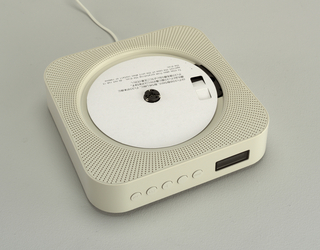 White plastic square body with rounded corners; face pierced for speaker; large central circular indentation with reader having center spindle to recieve and play CD; white power cord hanging from center bottom acts as on/off pull switch.