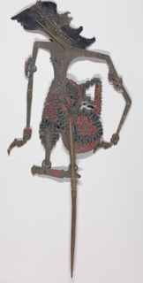 Female figure with elaborate coiffure extending down to shoulders, bracelets on wrists and ornaments on upper arms. Painted with red and blue, faded.