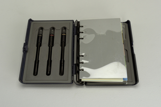 Rectangular black plastic case opening to reveal two colored pens and one pencil housed inside front cover, agenda and calendar pages held by binder rings in spine.