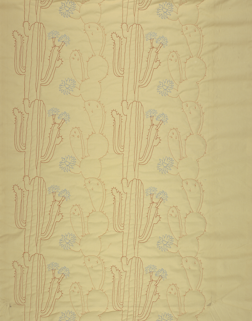 Tan cotton machine embroidered with repeat design of cactuses in red and blue.