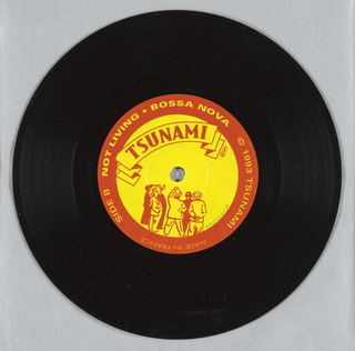 Black vinyl record for musical group Tsunami with circular paper labels on center of each side. Printed in red and yellow. Song titles (Side A: IN ANAME; Side B: NOT LIVING BOSSANOVA) and other information printed on red circular band, around yellow circle with group's name.